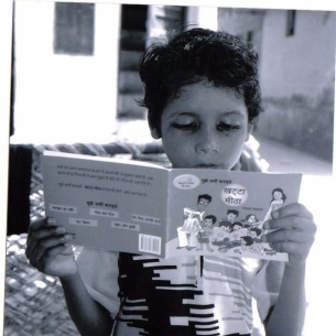 A_child_reading_a_book_by_Pratham_Books_-_Flickr_-_Pratham_Books
